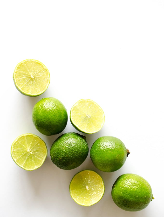 Limes cut in half on a white background