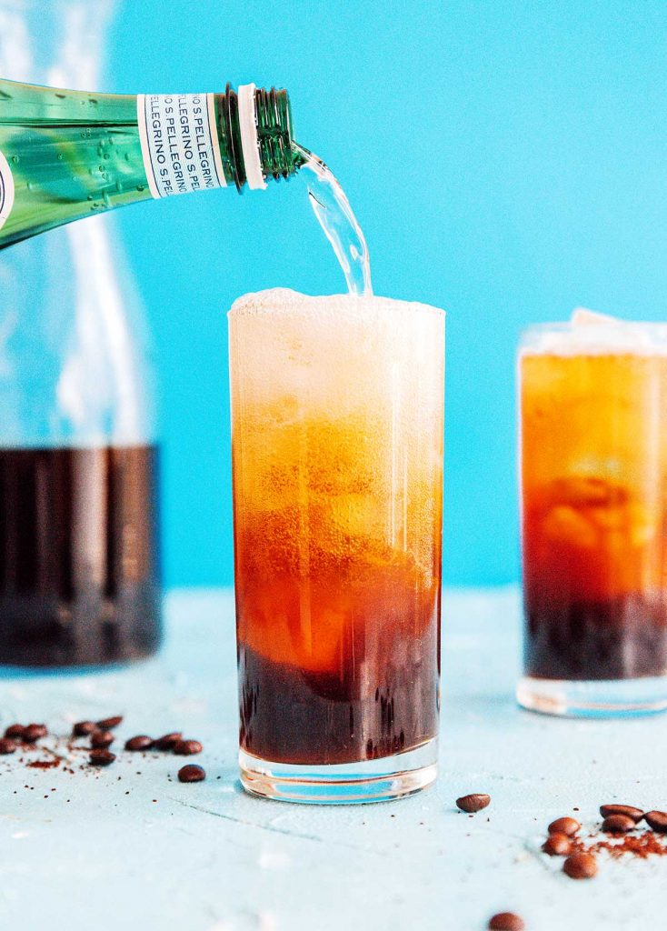 Fizzy coffee in a tall glass with a straw on a blue background
