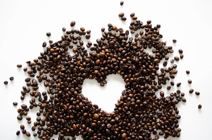 Coffee beans forming a heart on a white background