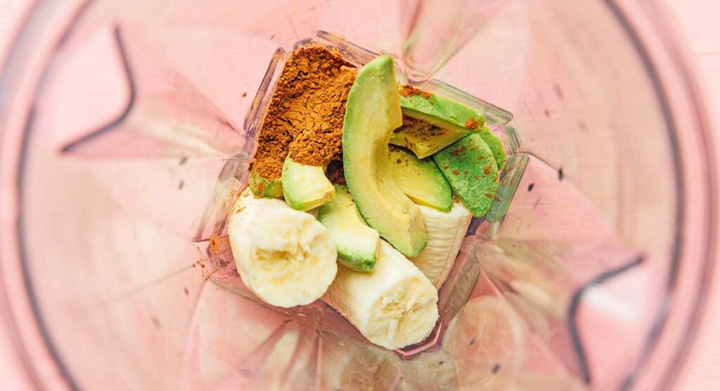 Avocado chocolate smoothie ingredients unmixed in a blender