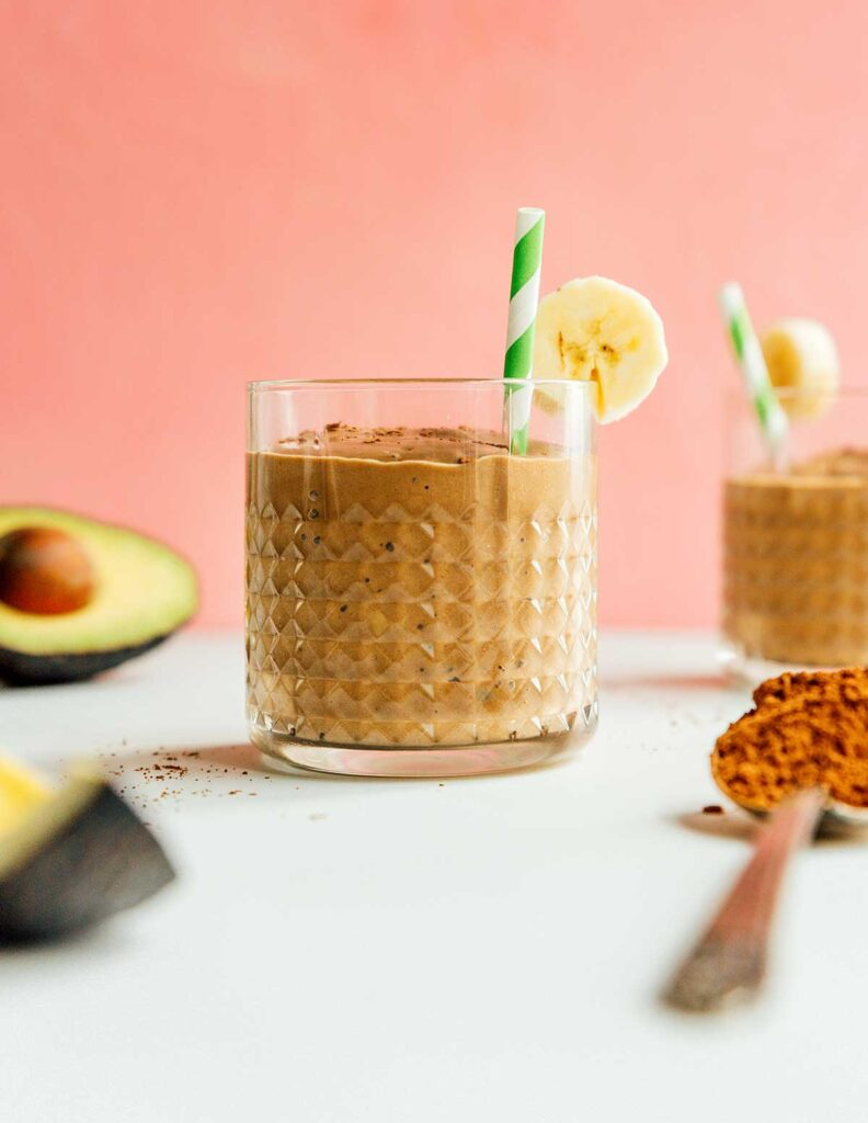 A glass filled with chocolate avocado smoothie and topped with a banana slice and a green and white striped straw
