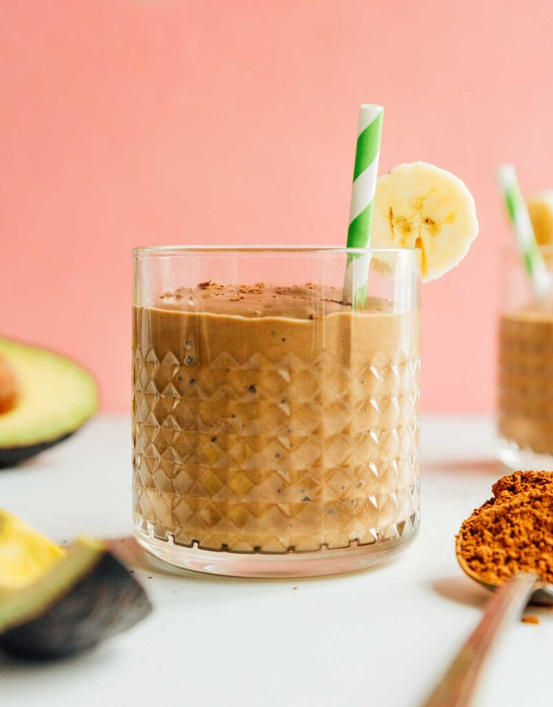 A glass filled with chocolate avocado smoothie and topped with a banana slice, cinnamon, and a green and white striped straw