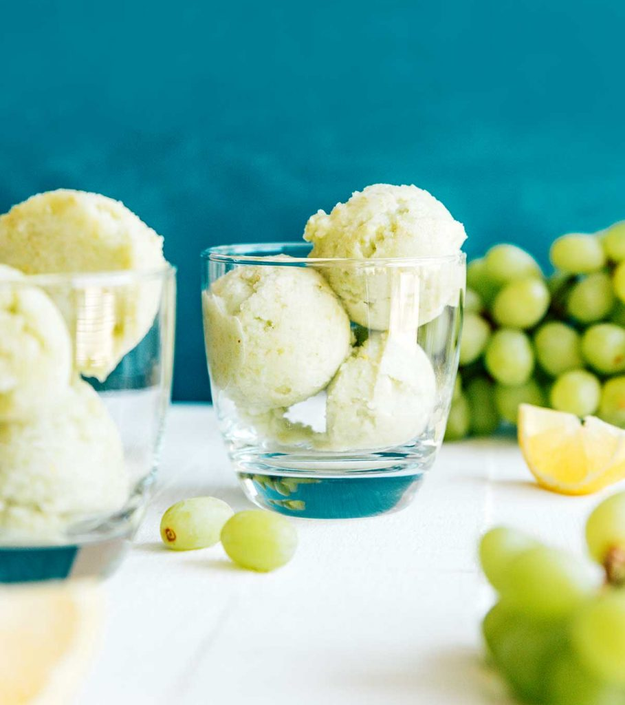 Scoops of green grape sorbet into a glass on a blue background