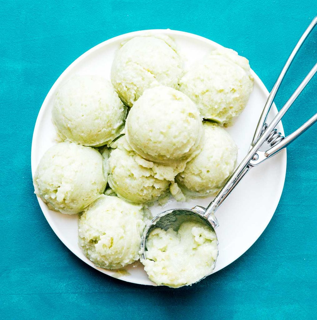 Scoops of green grape sorbet on a white plate on a blue background