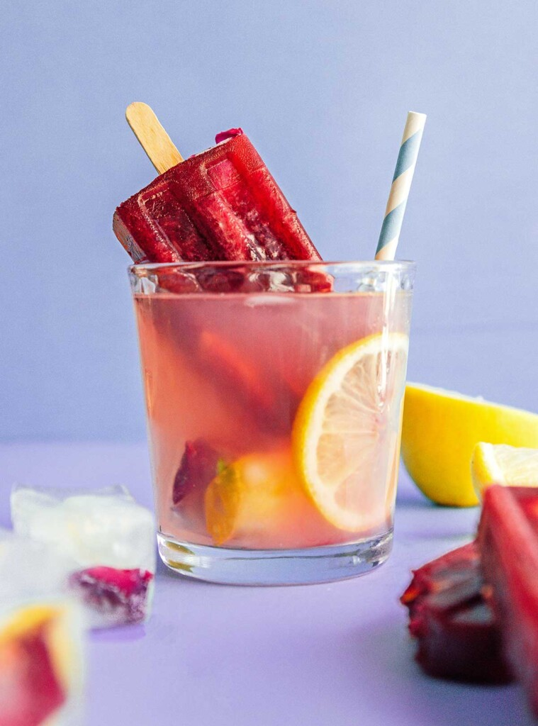 A glass of lavender lemonade filled with edible flower ice cubes and lemon slices and topped with a popsicle