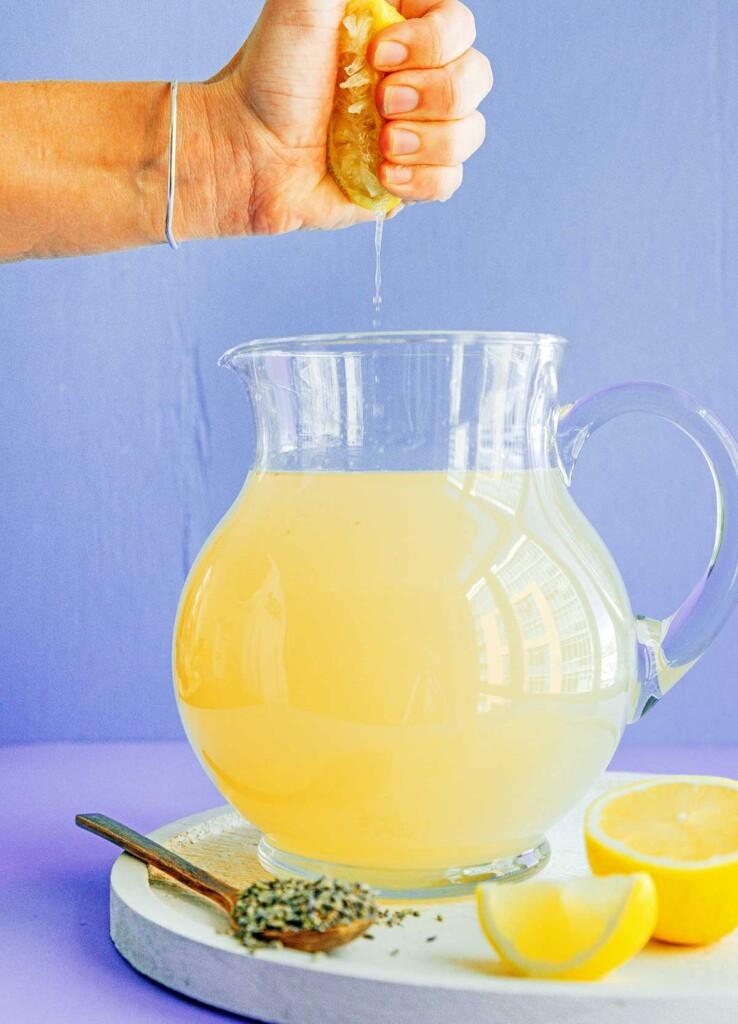 A hand squeezing lemon juice into a pitcher of lavender lemonade
