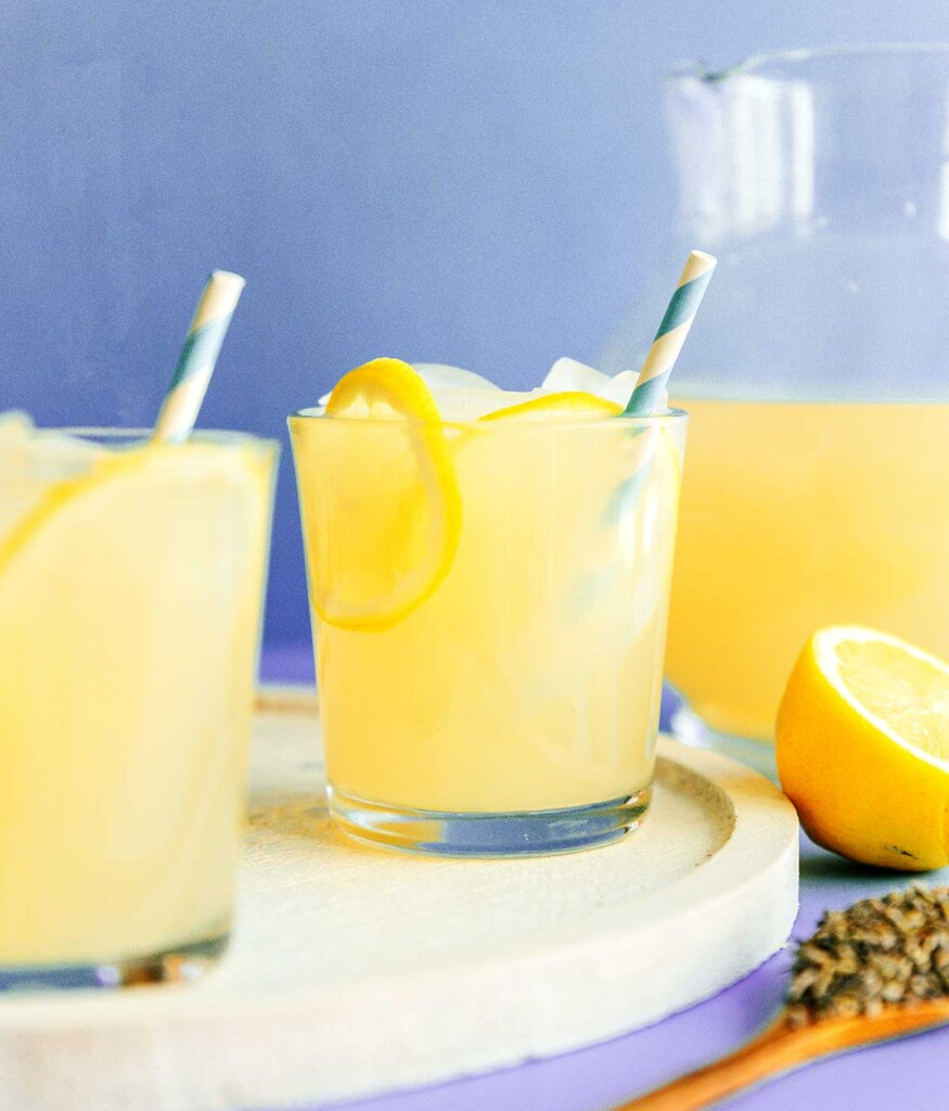 A glass of lavender lemonade topped with lemon slices