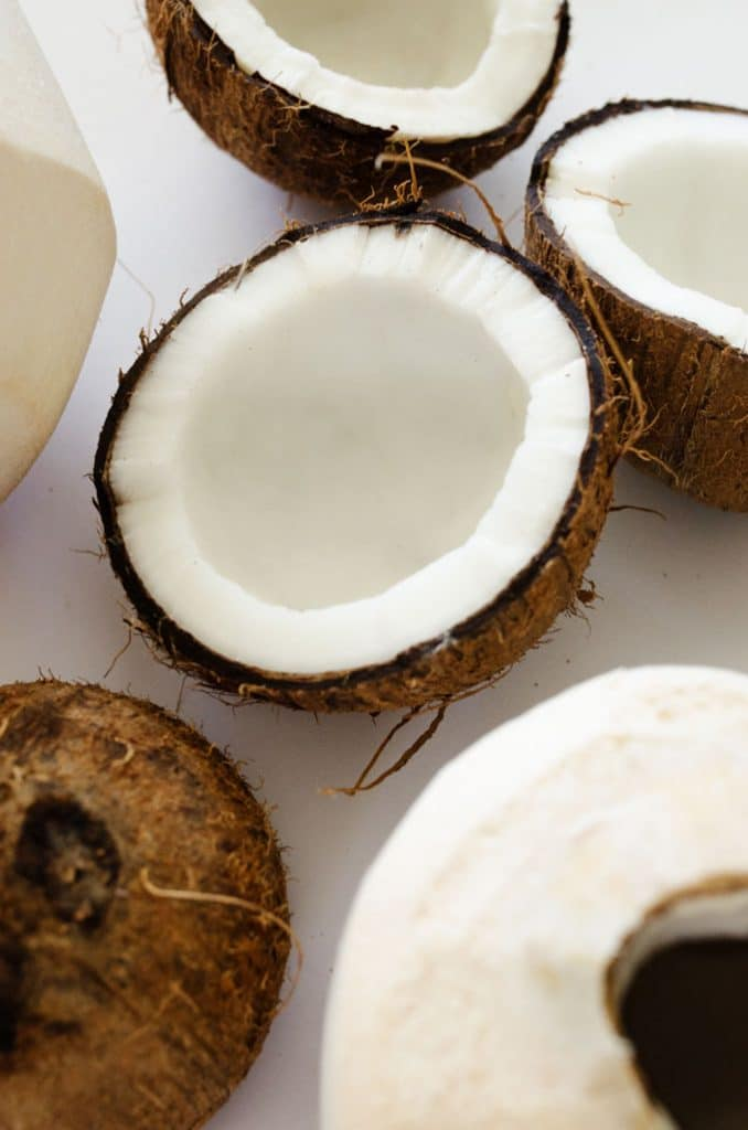 Picture of halved coconut shells on white background