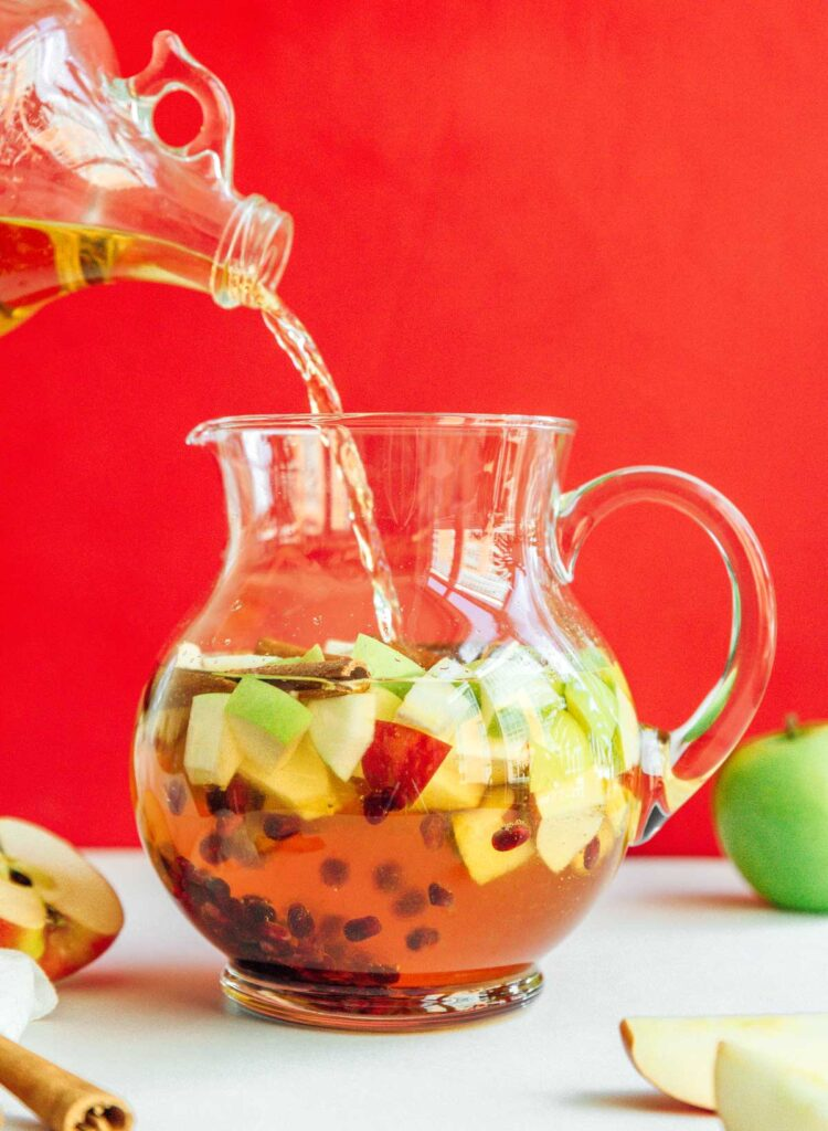 Pouring white wine into a pitcher filled with diced apples, cinnamon sticks, and pomegranate seeds