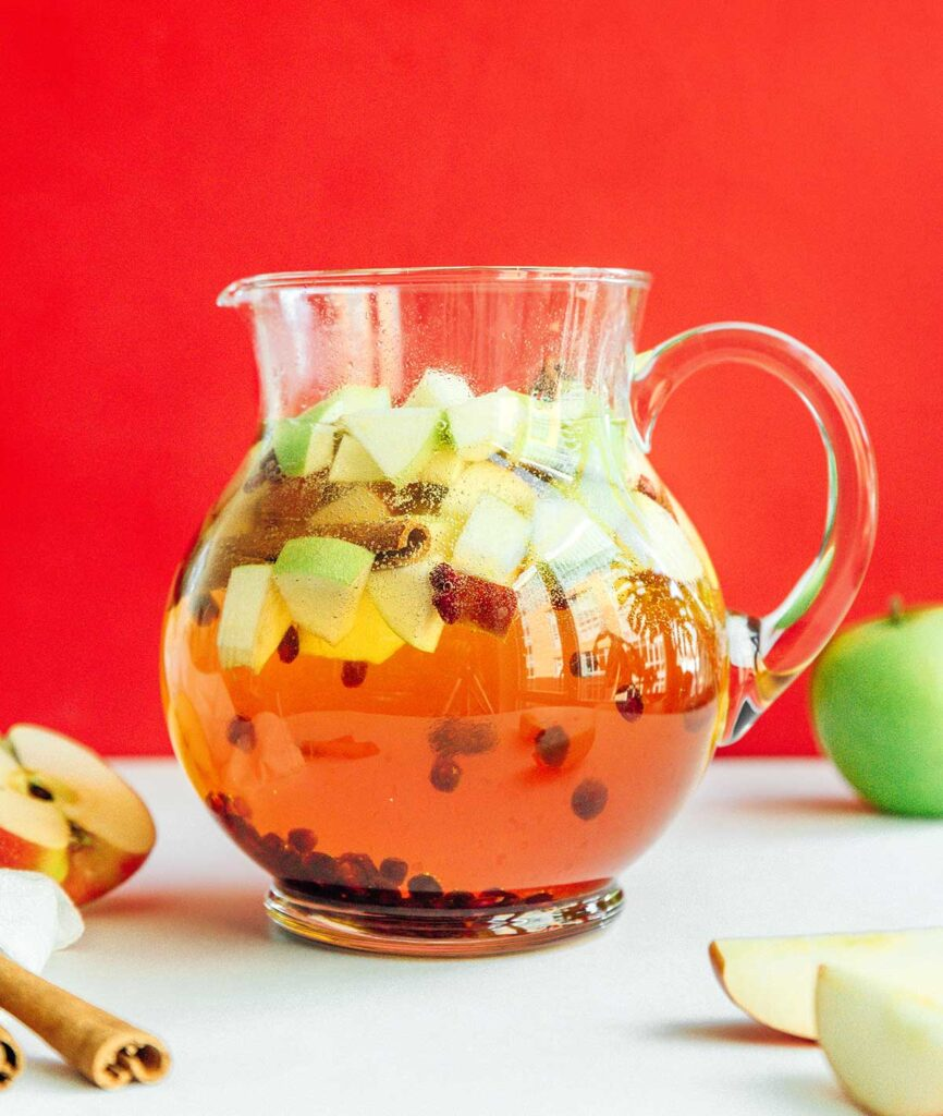 A pitcher filled with autumn apple sangria and garnished with diced apples, cinnamon sticks, and pomegranate seeds