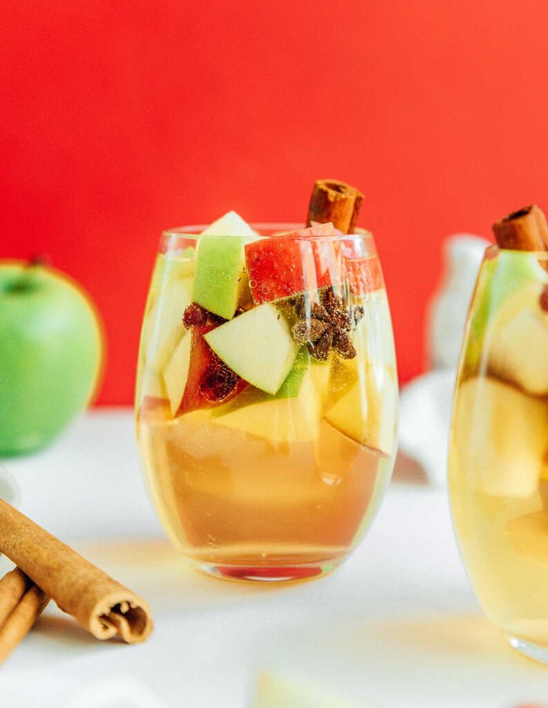 A wine glass filled with autumn apple sangria complete with apple pieces and cinnamon