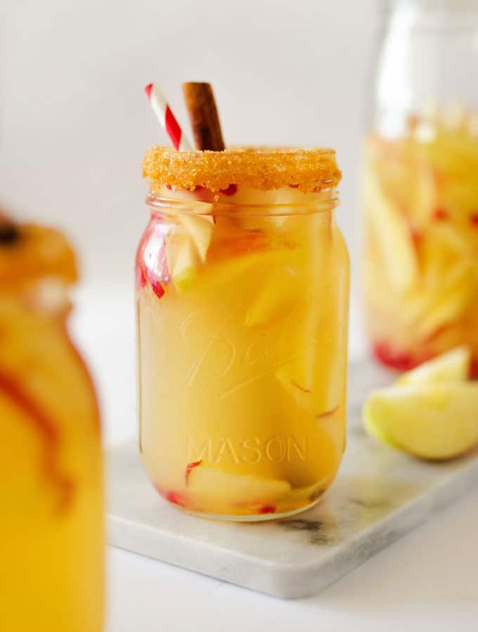 Autumn Apple Sangria in a glass with cinnamon and apples