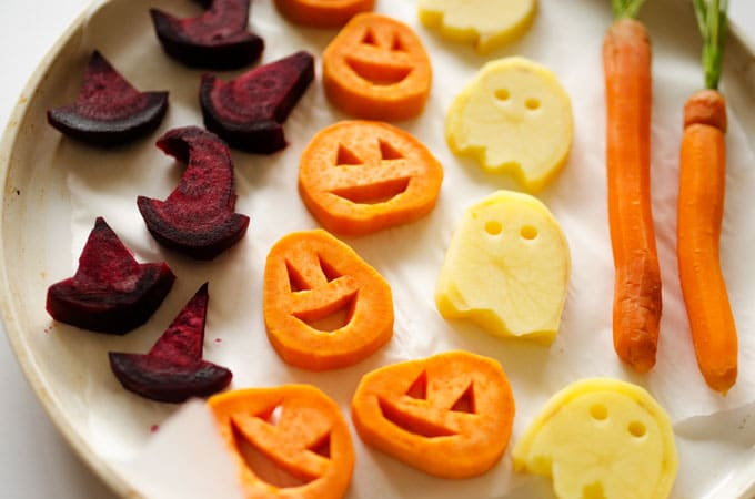 With sweet potato jack-o-lanterns, beet root witch's hats, and spooky potato ghosts, these Halloween Roasted Veggies are a healthy Halloween dinner recipe!