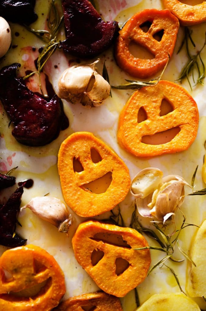 Vegetables shaped like spooky Halloween characters - With sweet potato jack-o-lanterns, beet root witch's hats, and spooky potato ghosts, these Halloween Roasted Veggies are a healthy way to celebrate!