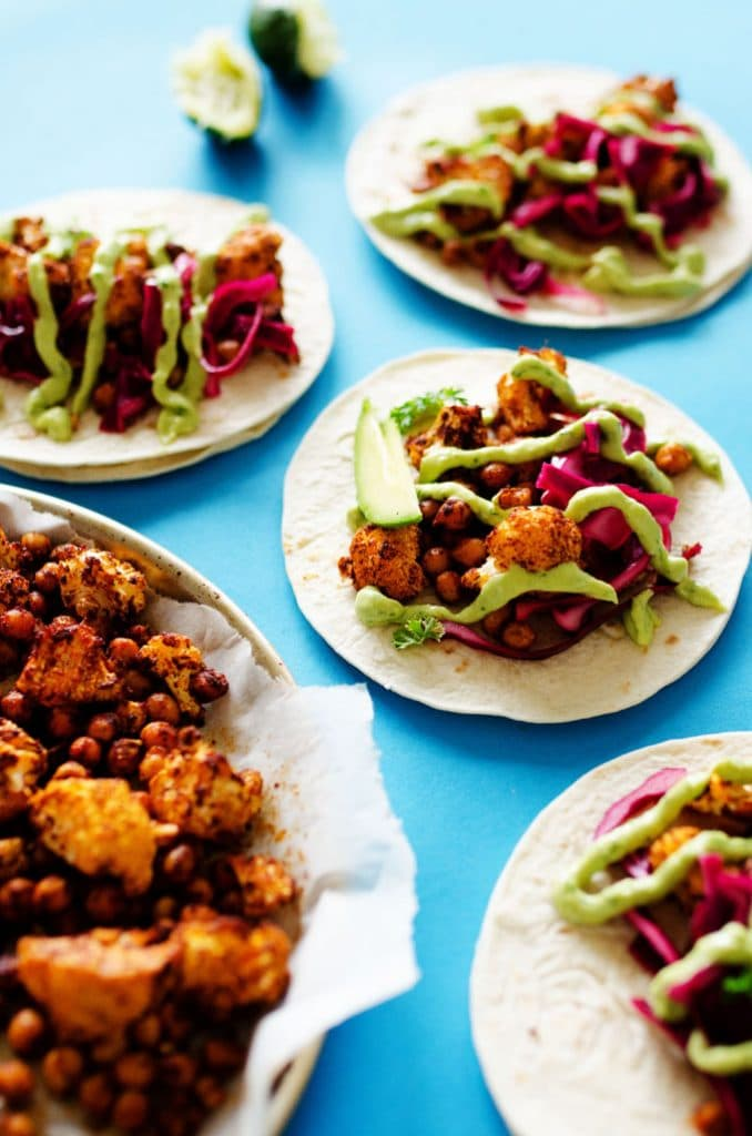 Cauliflower tacos with avocado sauce and red cabbage on tortillas
