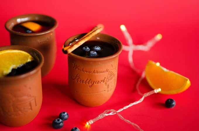 Experience the cozy German Christmas markets without ever leaving the comfort of your home with this Blueberry Gluhwein recipe! With only 5 ingredients, this is a simple alcoholic mulled red wine to warm your bones this winter. And you just need blueberries, cinnamon, and cloves to make this gluten-free, vegan gluehwein!