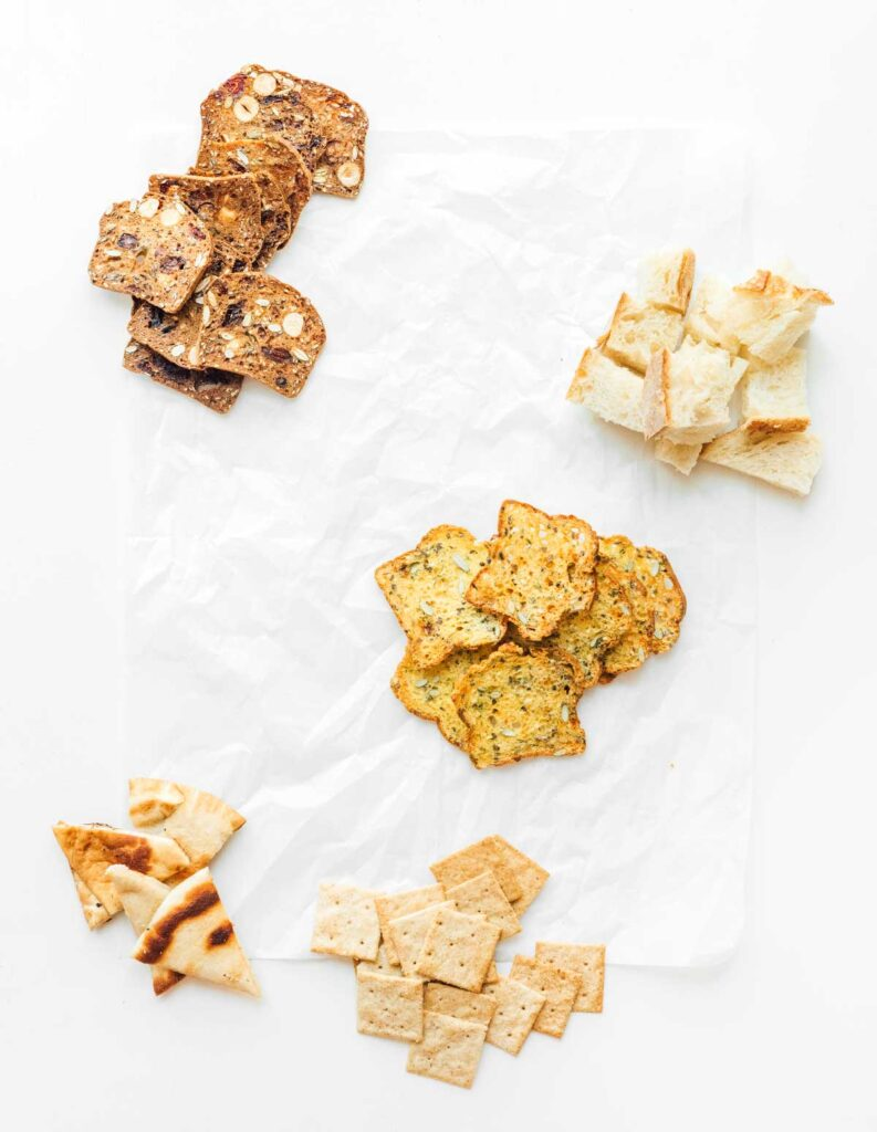 The start to a cheese board with 4 types of crackers and bread pieces spread out in neat groups