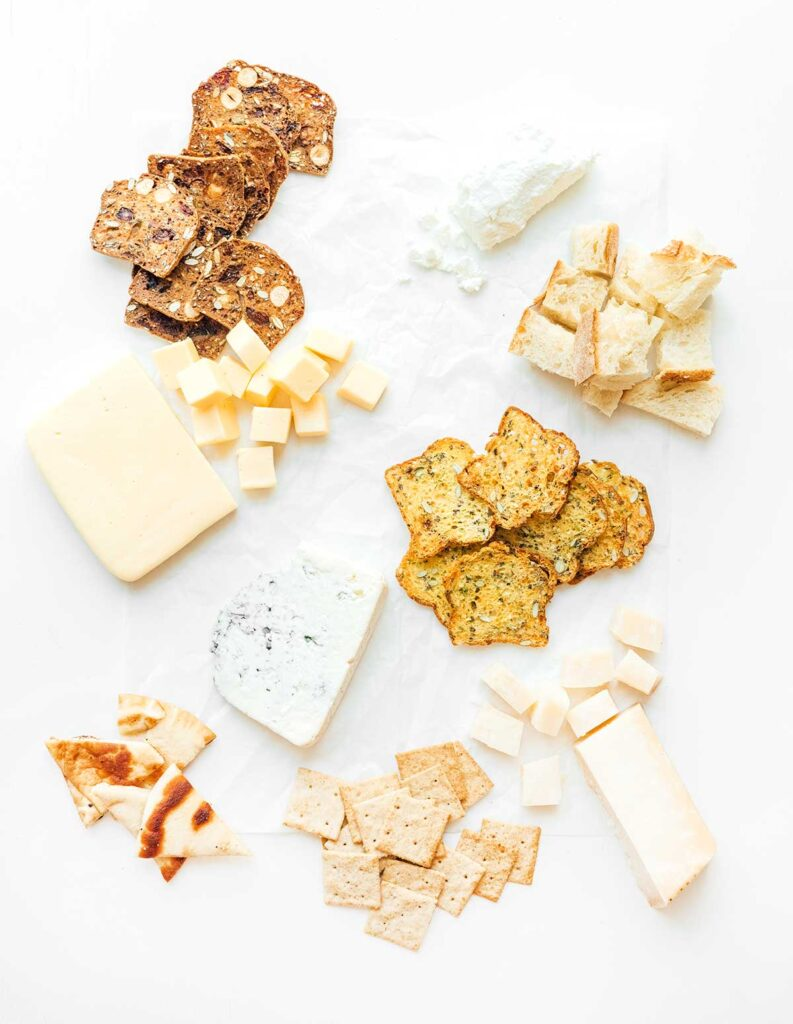 The start to a cheese board with 4 types of crackers and bread pieces spread out in neat groups with four types of cheese placed in between