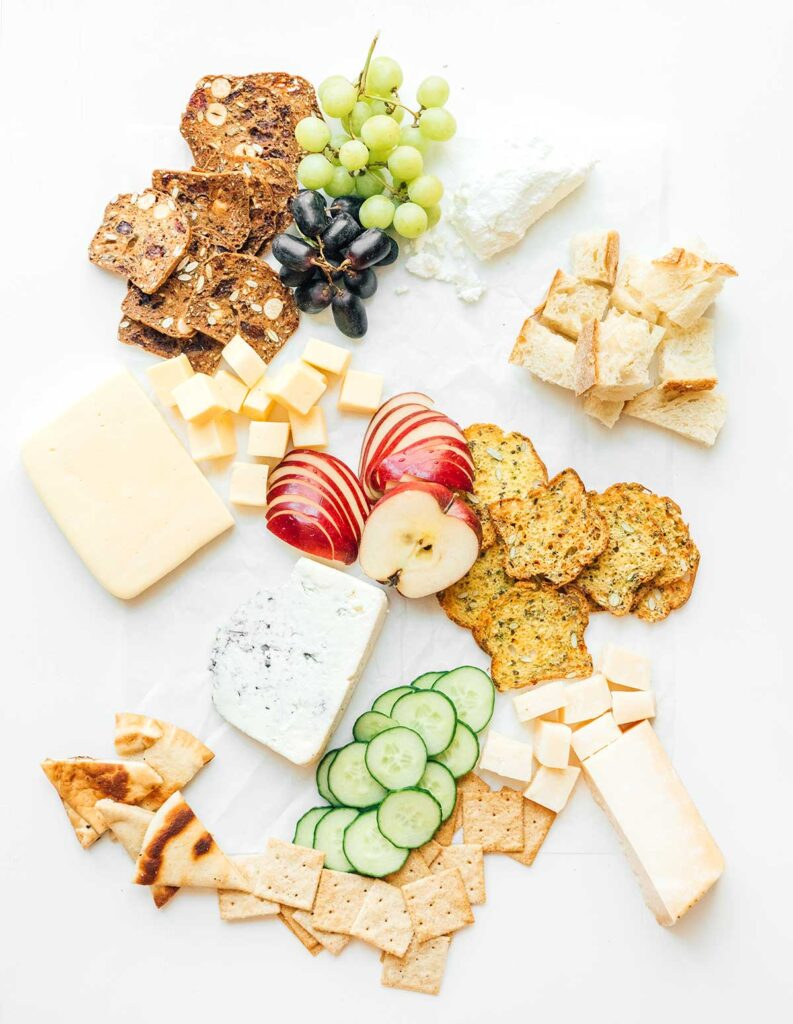 A charcuterie board that is coming together with crackers, breads, fruits, veggies, and cheeses