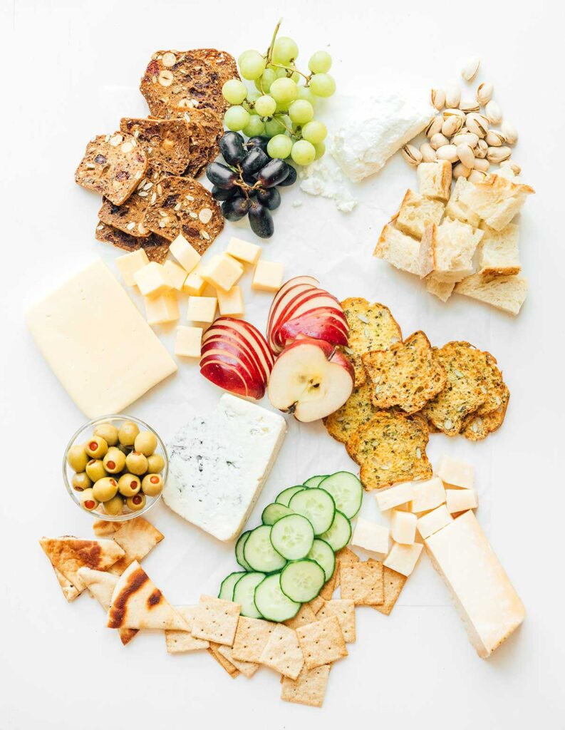 A charcuterie cheese platter that is coming together with crackers, breads, fruits, veggies, cheeses, nuts, and olives