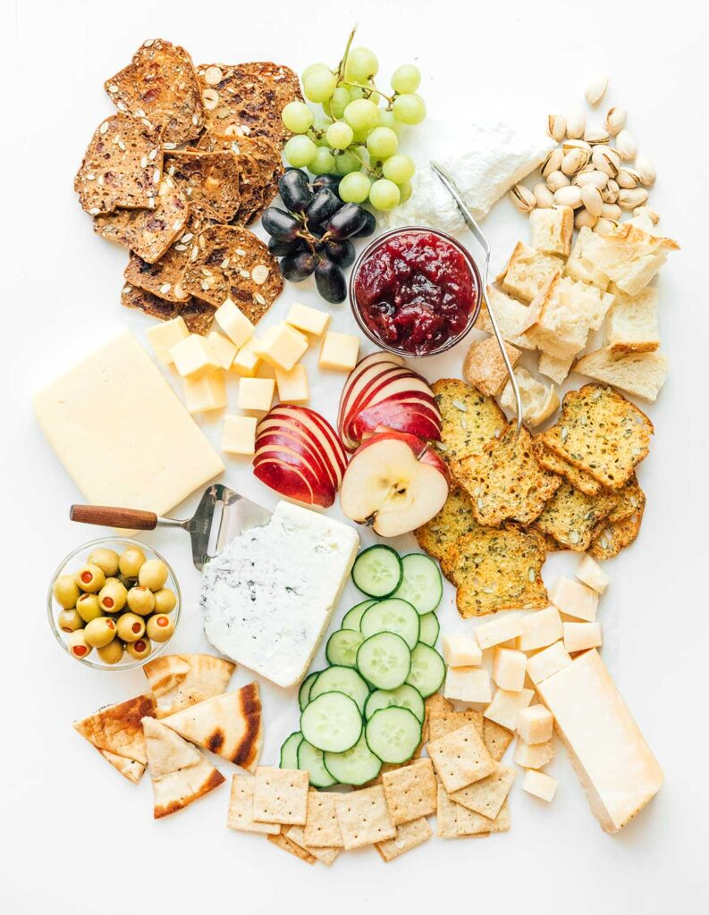 A cheese board complete with various crackers, cheeses, fruits, veggies, spreads, nuts, and olives