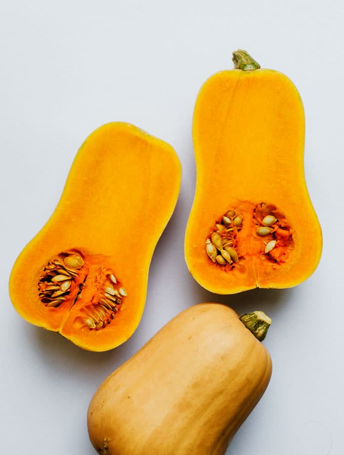 Butternut squash cut in half on a gray background