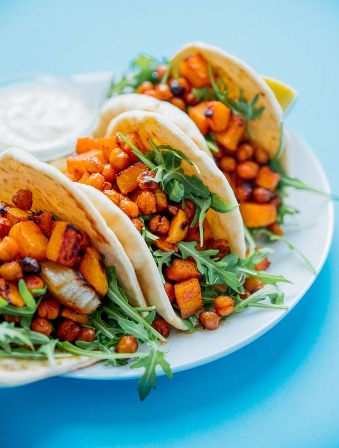 Butternut wraps on a plate with blue background - Spicy, savory flavor all wrapped up in warm flatbreads is the name of the game with these Roasted Butternut Chickpea Hummus Wraps!