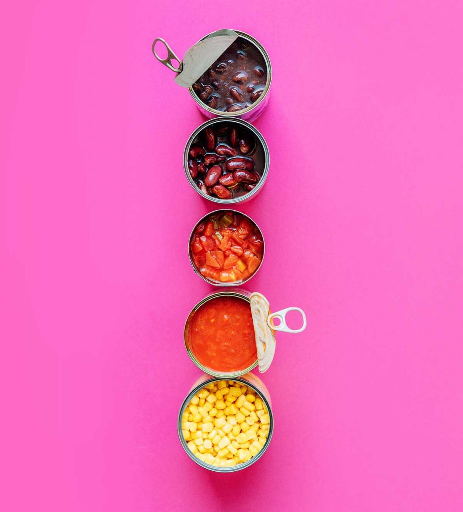 Cans used to make taco soup on a pink background