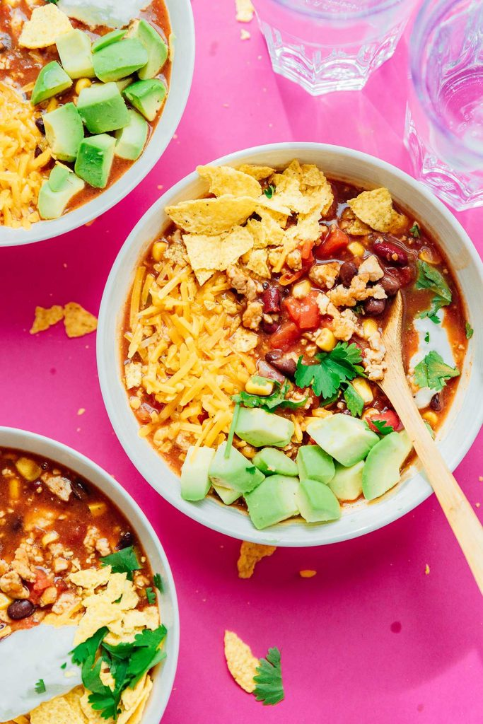 Taco soup in a bowl on a pink background topped with avocado and chips