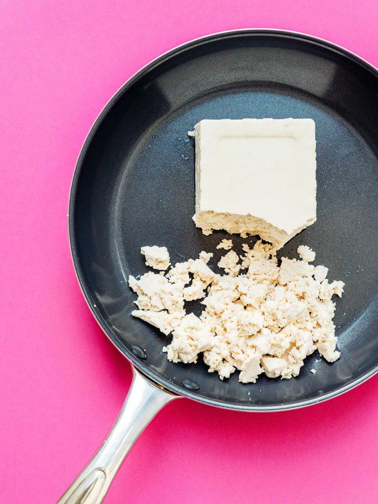 Crumbling tofu in a pan