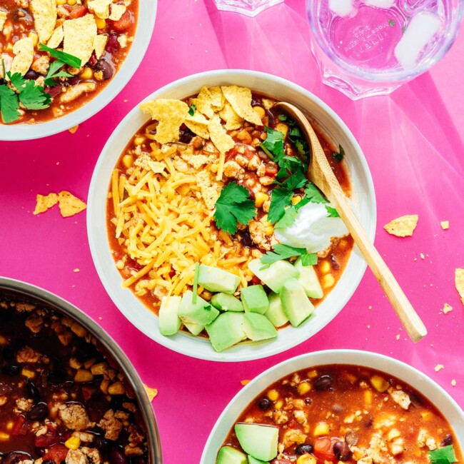 Taco soup in a bowl on a pink background