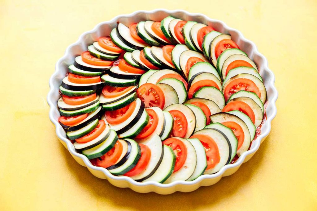 Raw layered vegetables in a tart pan