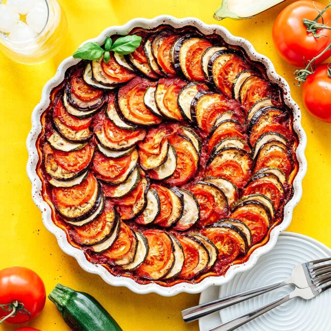 Layered vegetable tian in a tart pan on a yellow background