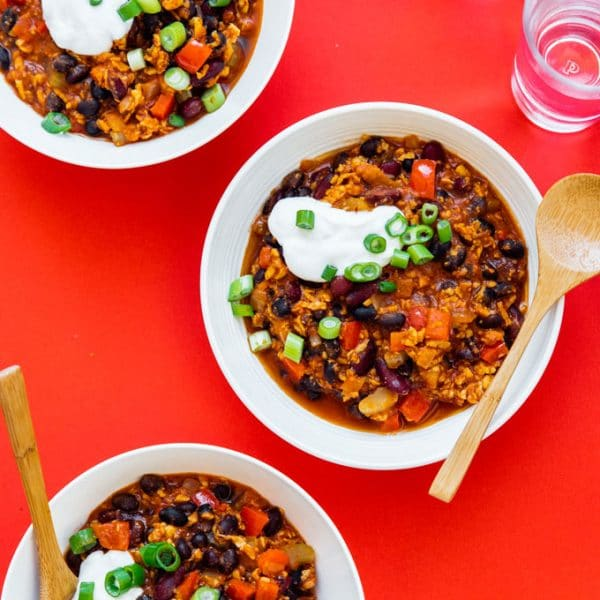Vegan tempeh chili in white bowls on a red background