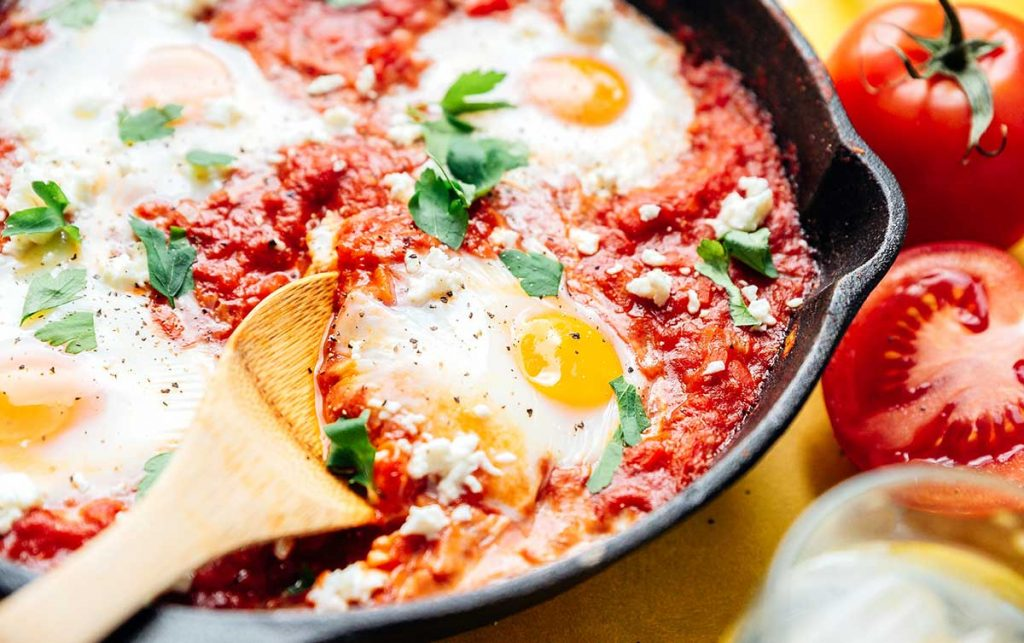 Close up photo of cooked eggs in tomato sauce in a cast iron skillet on a yellow background