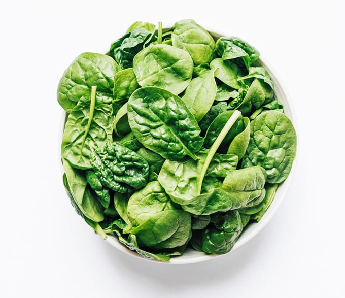 Spinach leaves in a bowl on a white background
