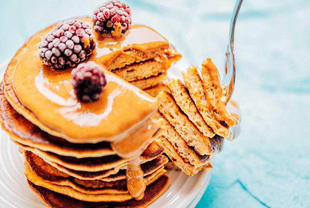 Paleo pancakes with almond butter and berries on a blue background