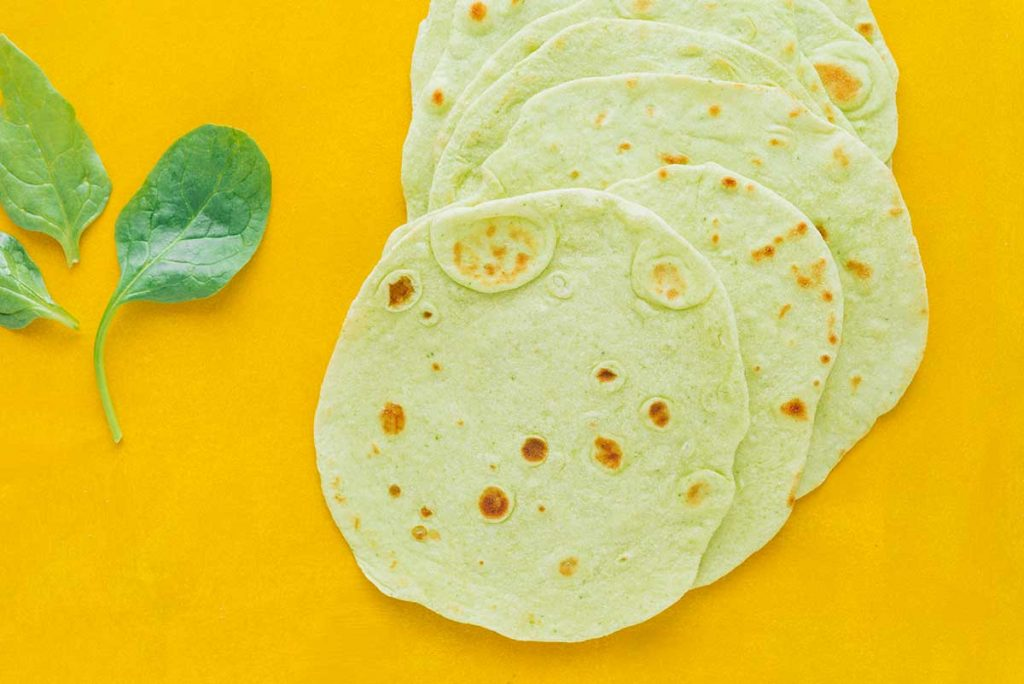 Green tortillas laying with a spinach leaf