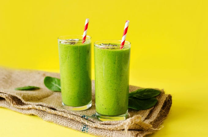 Green smoothie recipe photo in a glass with a striped straw and a yellow background