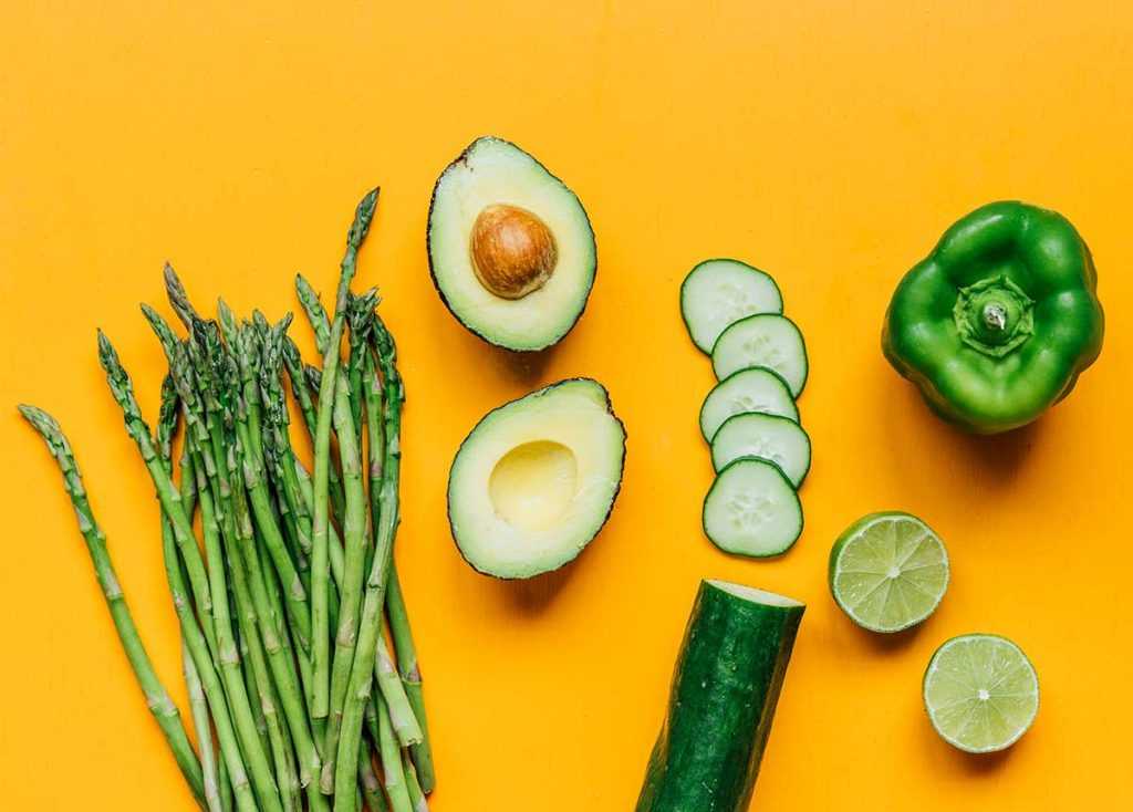 Asparagus, a halved avocado, a sliced cucumber, a halved lime, and a green bell pepper arranged on an orange background