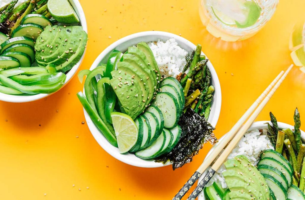 A complete green goddess sushi bowl containing rice, asparagus, sushi paper, cucumber, avocado, green bell pepper, and lime