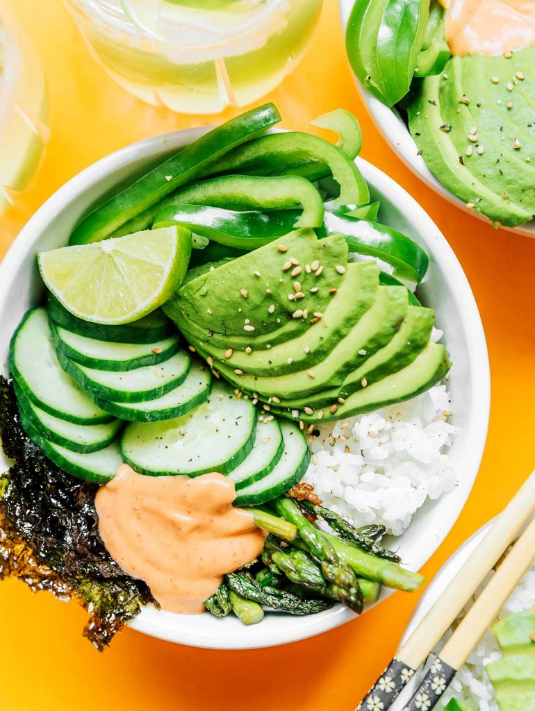 A complete green goddess sushi bowl containing rice, asparagus, sushi paper, cucumber, avocado, green bell pepper, lime, and sriracha mayo