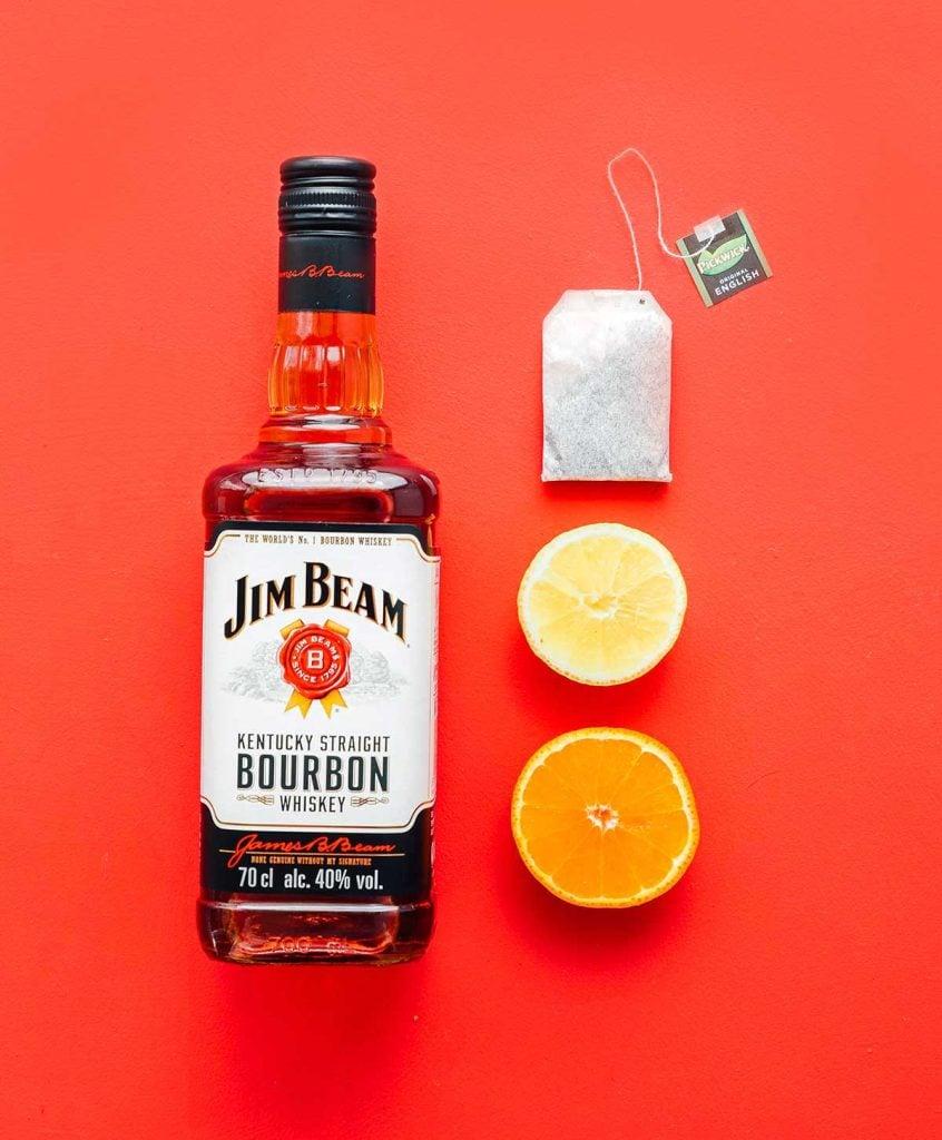 Jim Beam bourbon, tea bag, lemon, and orange on red background