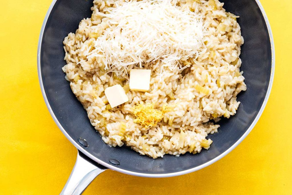 Adding butter and cheese to a pan of risotto