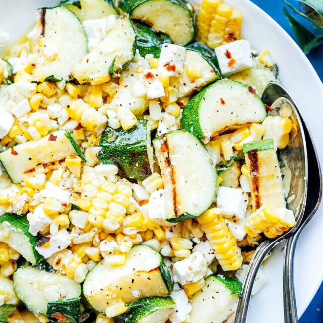 Zucchini corn salad on a white plate with serving spoons