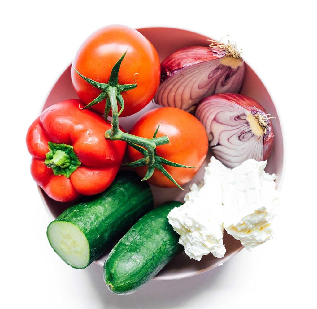 A bowl filled with two tomatoes, a red onion chopped in half, two blocks of feta cheese, a cucumber chopped in half, and a red bell pepper