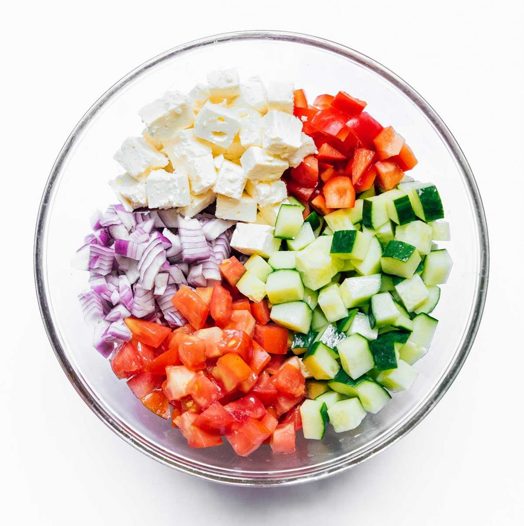 A glass dish filled with chopped salad ingredients including feta, red bell pepper, cucumber, tomatoes, and red onion