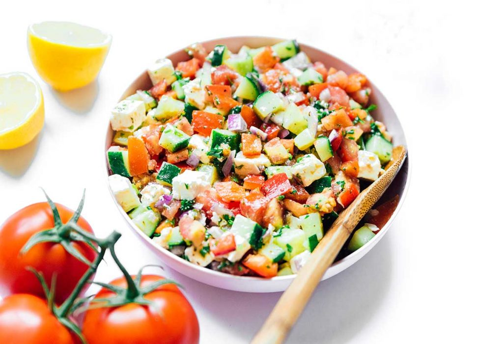 A serving dish filled with a freshly mixed summer veggie salad
