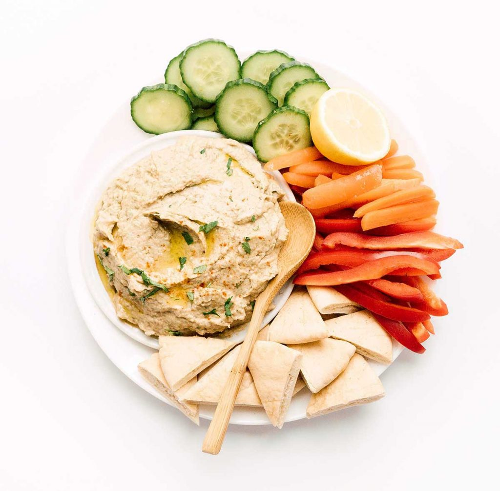 Eggplant baba ganoush with veggies and pita on a white background