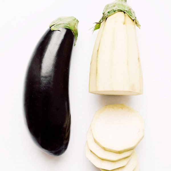 Photo of two eggplants, one peeled and sliced, on a white background